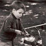 Boy using a hose to clean a tricycle