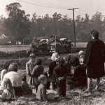 Children and teacher looking at an old farm