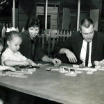 Children and Adults playing with a wooden train set