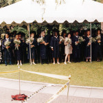Older students in graduation robes under a tent