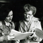 Two women looking at a periodical book