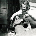Woman with a paint brush and a can of wood stain