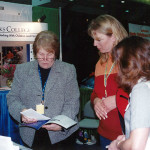 Tradeshow booth with 3 women talking