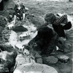 Children playing with toy boats in a creek