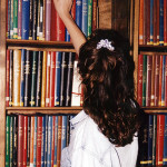 Young Woman Reach for a Book on a Shelf