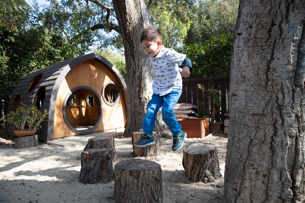 Child jumping in outdoor learning environment