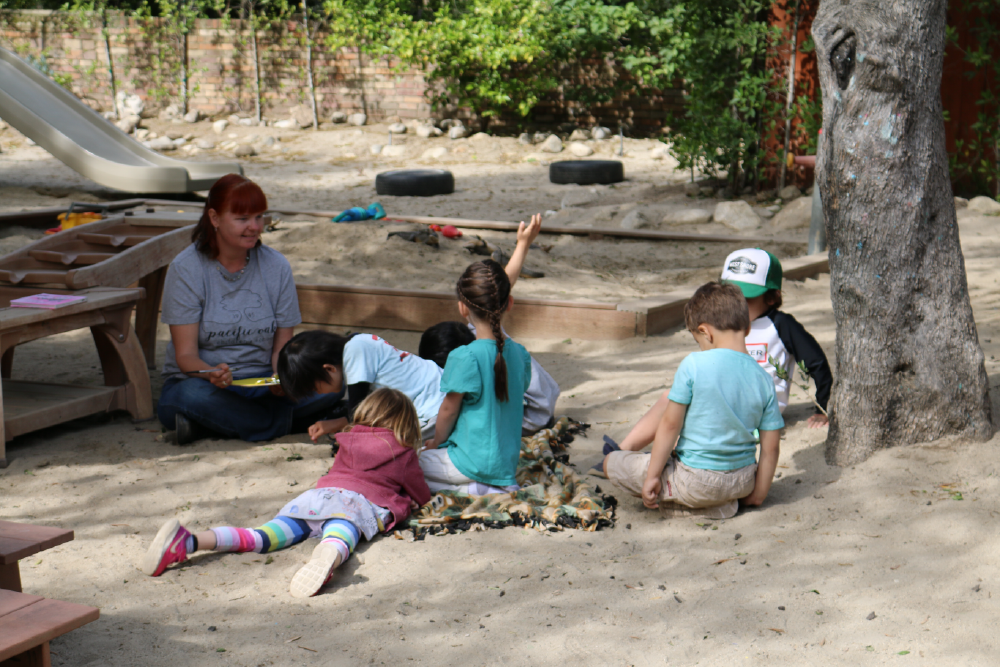 Children learning with teacher outdoors